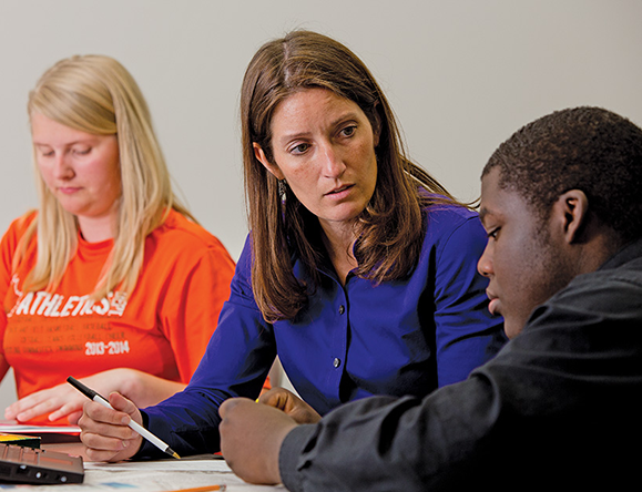 Sara Donathen-Smith, an iGrad coach at Columbus East High School, works with students Brooke Tames and Rico Lewis. Both teens admit they were struggling before their involvement with iGrad, an enhanced counseling program that tackles the social, academic and attitudinal problems that often cause students to drop out.