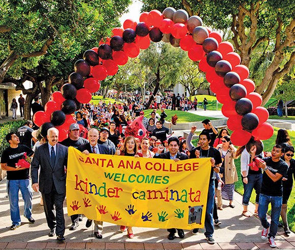 Holding the banner and leading the 2014 Kinder Caminata parade are (from left): Raúl Rodriguez, chancellor of the Rancho Santiago Community College District (RSCC); Rick Miller, superintendent of the Santa Ana Unified School District; U.S. Rep. Loretta Sanchez (D-Calif.); José Solorio, president of the RSCC board of trustees, and Jorge Sandoval, student government president at Santa Ana College.